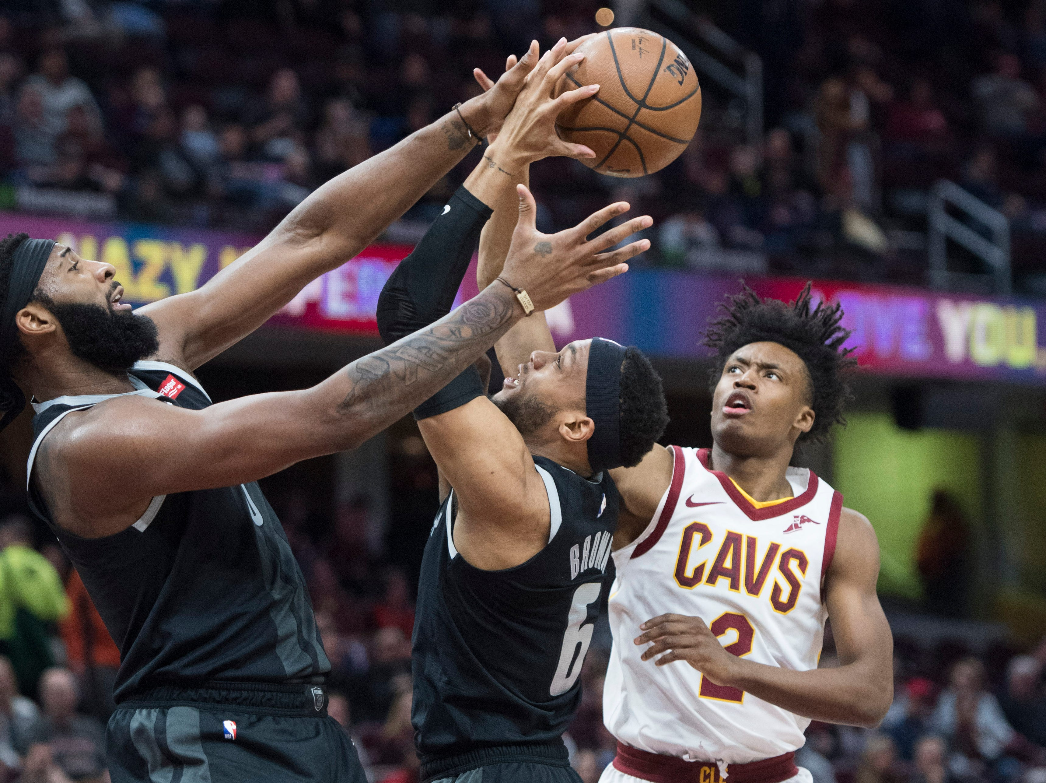 Detroit Pistons' center Andre Drummond, left, and guard Bruce Brown, center, go for a rebound against Cleveland Cavaliers' guard Collin Sexton in the first half of an NBA basketball game,