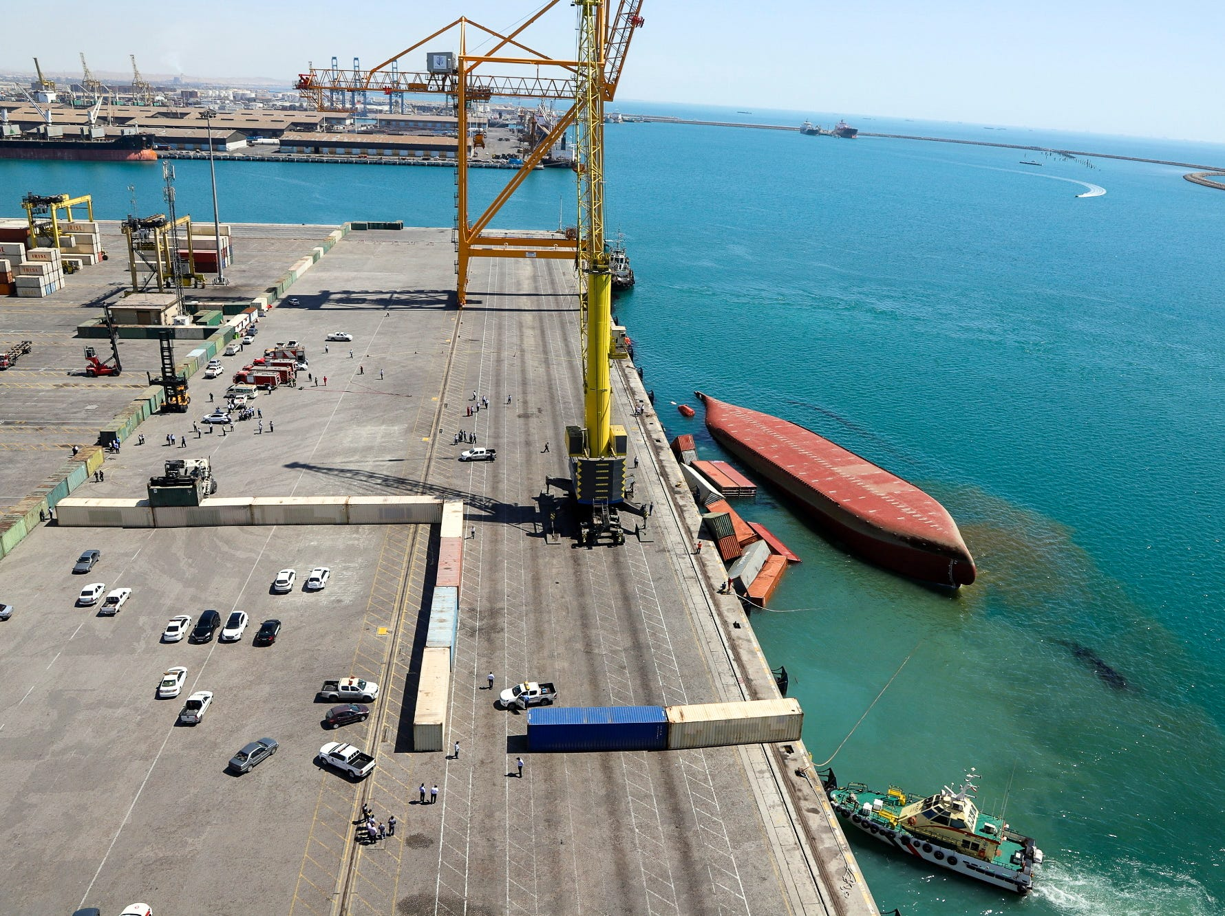 A capsized cargo ship bobs next to a dock in the southern port of Bandar Abbas, Iran, Tuesday, March 19, 2019. Iranian state TV says careless loading of cargo flipped the vessel, sending port workers scrambling to retrieve some of the 153 submerged containers.