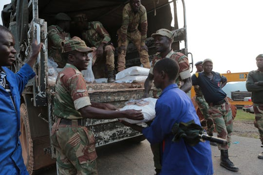 Soldiers handout food supplies to people in Chimanimani, southeast of Harare, Zimbabwe, Monday, March 18, 2019.