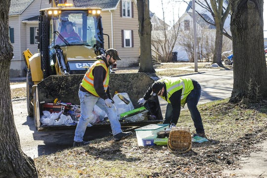 Fond du Lac Department of Public Works employees Jack Mohr (in front end loader), Jeff Gassner and Brian Labota pick up bulk flood damaged garbage Tuesday, March 19, 2019 on Gould Street in Fond du Lac, Wis. Ice jams on the east branch of the Fond du Lac River and heavy rain caused widespread flooding problems in the city on Thursday the 14th. Doug Raflik/USA TODAY NETWORK-Wisconsin