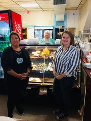 Patty Cakes Village Bake Shop owners Nancy Calvert and Kelly Burnworth stand in front of a display of baked items while cake decorator Lisa White stands in the background