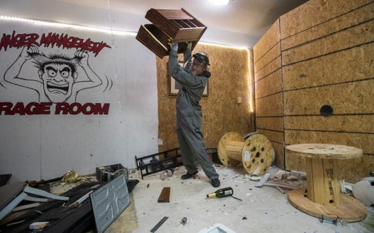 Fort Myers resident Michael Tessmer hurdles a small cabinet while at Anger Management Rage Room Monday evening, 3/18/19. The month old business aims to give customers an opportunity to vent their anger and destroy available furniture, glassware and assorted items.