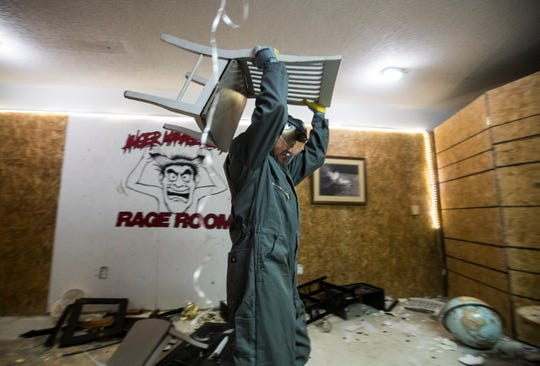 Fort Myers resident Michael Tessmer hurdles a chair while at Anger Management Rage Room Monday evening, 3/18/19. The month old business aims to give customers an opportunity to vent their anger and destroy available furniture, glassware and assorted items.