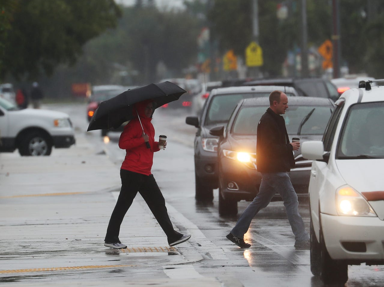 Pedestrians try to stay dry on Fort Myers Beach on 3/19/2019. A front is moving through the area and dropping light rain throughout Southwest Florida.