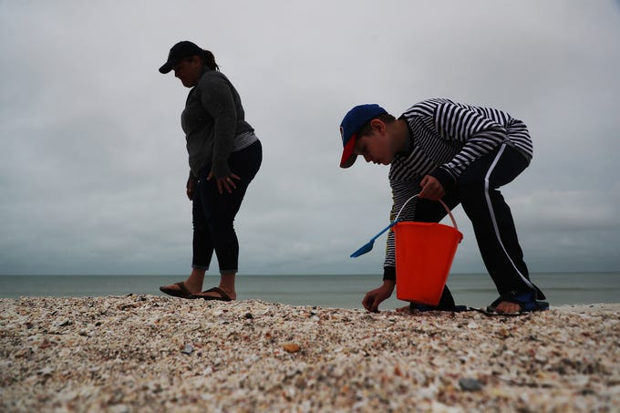 """Amy Gross and her son Jimmy Gross,13, from Johnstown, Pennsylvania shell the northern part of Bonita Beach on Tuesday 3/19/2019. """"The rain and bad weather doesn't bother us,"""" It's nice being by ourselves,"""" said Amy."""