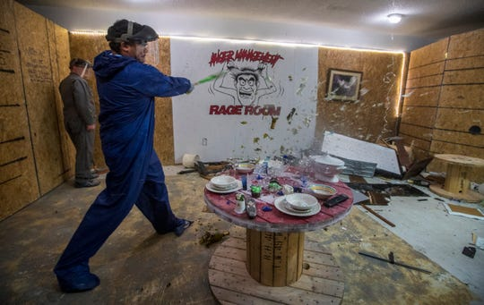 Ozzie Morrobel swings a baseball bat and shatters several wine bottles while participating in a session at Anger Management Rage Room in Fort Myers Monday evening, 3/18/19. The month old business aims to give customers an opportunity to vent their anger and destroy available furniture, glassware and assorted items.