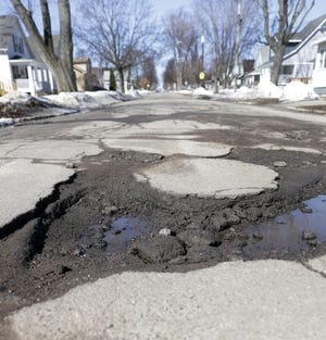 Potholes stretch across the 1100 block of Chicago Street on March 19 in Green Bay.