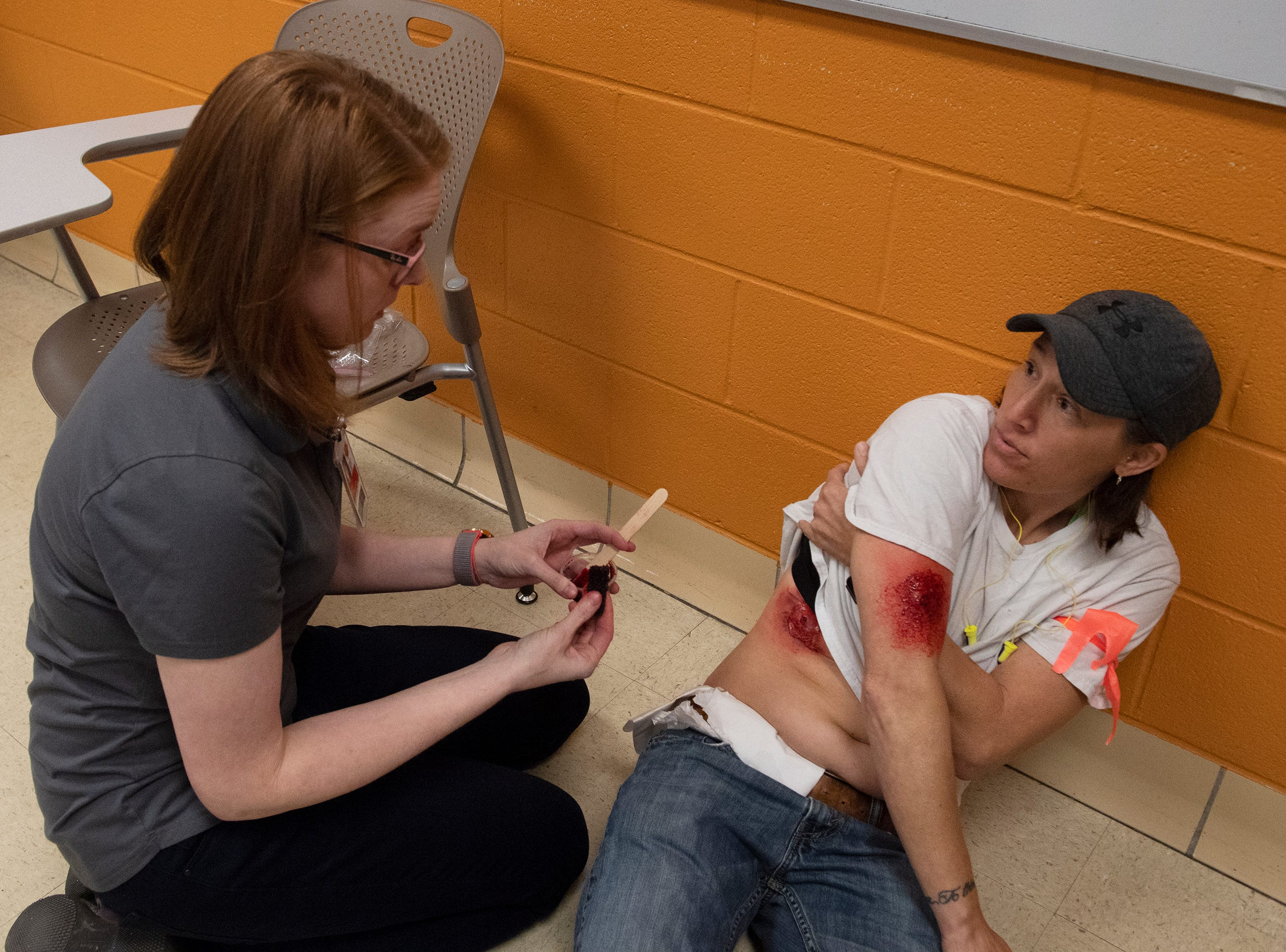 Jennifer Thackston (left), a paramedic and firefighter at Clemson University, applies make-up to simulate wounds on Jennifer Dickson, from the Fork Rescue Squad, in preparation for an active shooter exercise at Clemson Tuesday, Mar. 19, 2019. Dickson was one of the many people role-playing as victims inside Daniel Hall.