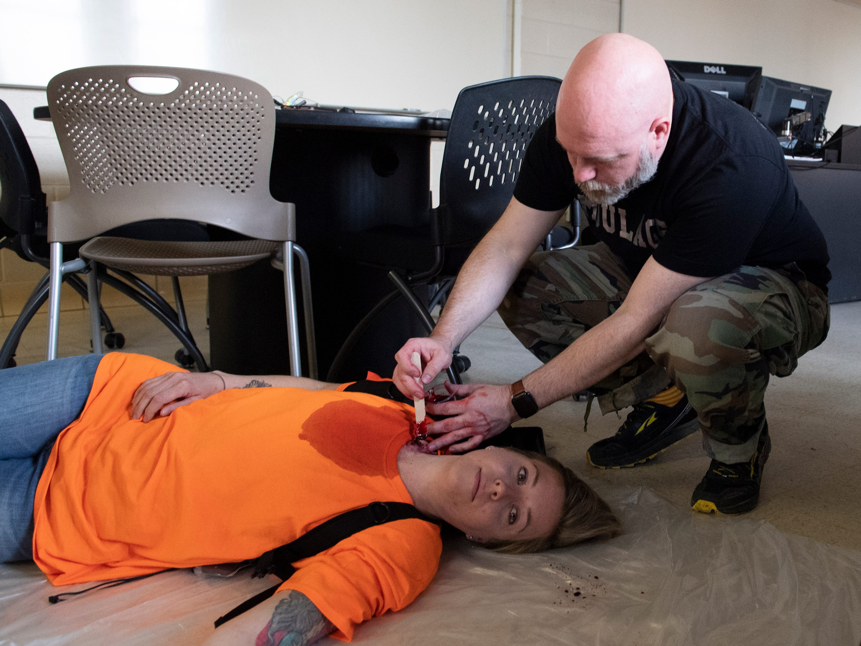 William Enfinger, from MEDNAX's simulation program,  applies make-up to imitate wounds on Heather Mullen in preparation for an active shooter exercise at Clemson University Tuesday, Mar. 19, 2019. Dickson was one of the many people role-playing as victims inside Daniel Hall.