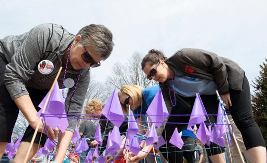 From left, Lenore Pankowski from Townville, Tammy McCraw from Boiling Springs, Lisa Martin from Seneca, and Emily Roberts from Walhalla, place purple flags in North Green after the Out of the Darkness Clemson University Campus Walk Saturday, Mar. 2, 2019.