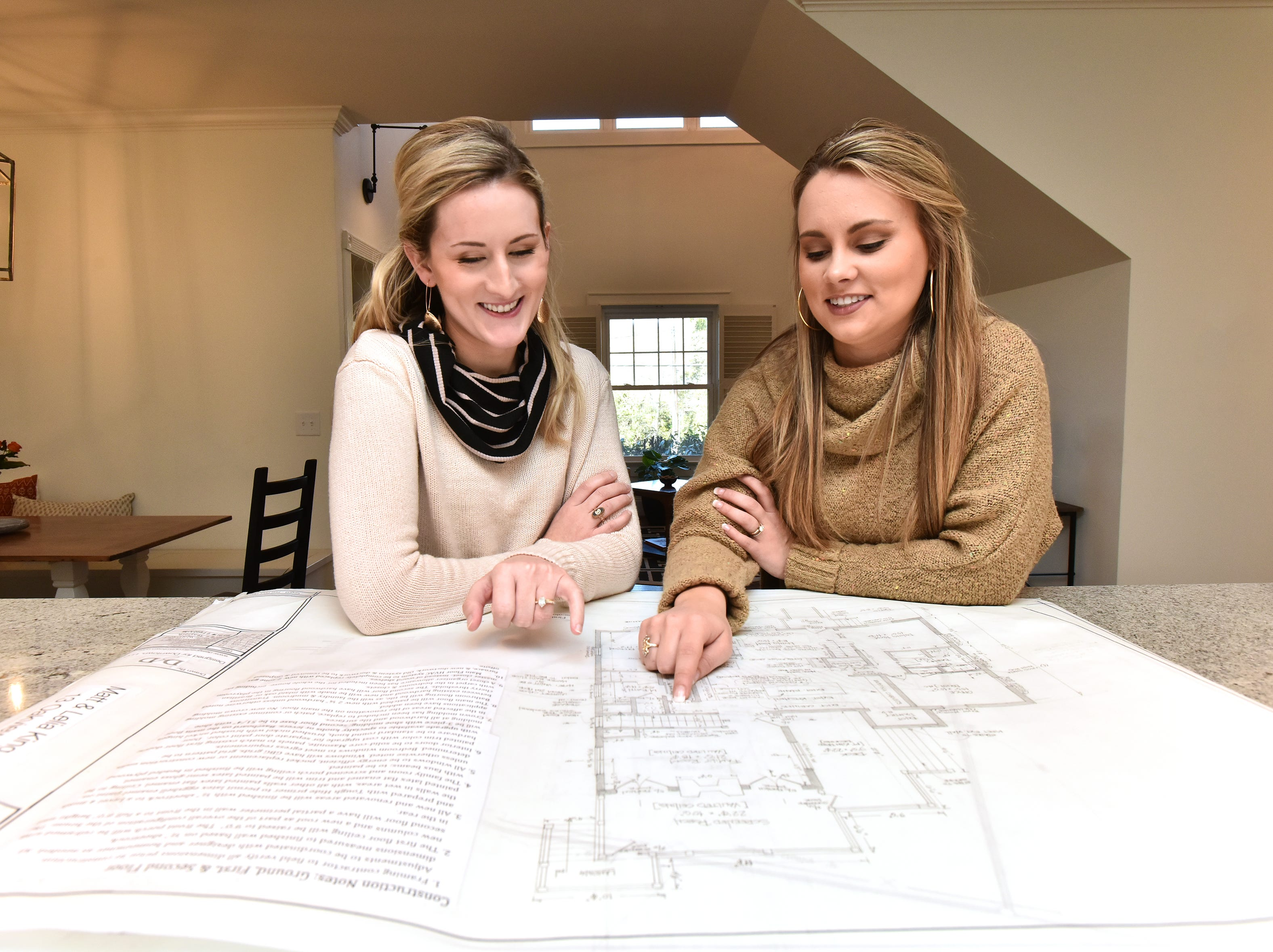 Designers Emily Infinger, left, and Lenzi Lee of Designed for Downtown look over floor plans in a Greenville family's home that they recently remodeled.