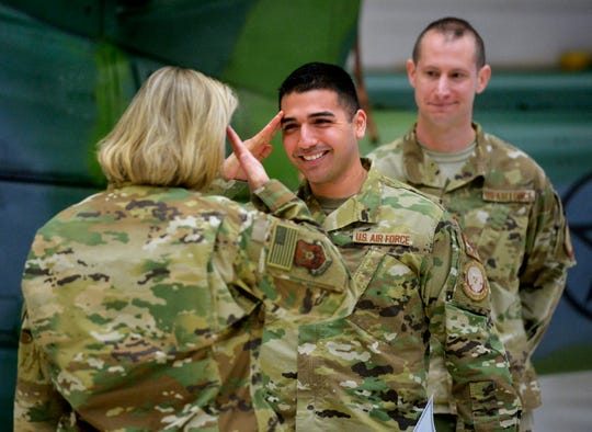 Staff Sergeant Richard Corpus-Munoz salutes Colonel Jennifer Reeves, commander of the 341st Missile Wing, during a recognition ceremony for 14 airmen involved in three seperate cilvilian rescues this winter.  Munoz was a part of a security forces helicopter crew that spotted and then helped dig out a stranded motorist on a remote Montana road in early March.