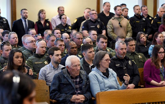 Family members of one  of the victims in last week's shootings in Missoula and Evaro, sit in Missoula County Justice Court in Missoula, Montana, Monday, March 18, 2019, backed by dozens of law enforcement officers from the Montana Highway Patrol and other jurisdictions, for the initial appearance of Johnathan Bertsch, 28, charged with one count of deliberate homicide and three counts of attempted deliberate homicide. Bertsch killed one man and wounded three others including Montana Highway Patrol Trooper Wade Palmer. (Kurt Wilson/The Missoulian via AP)