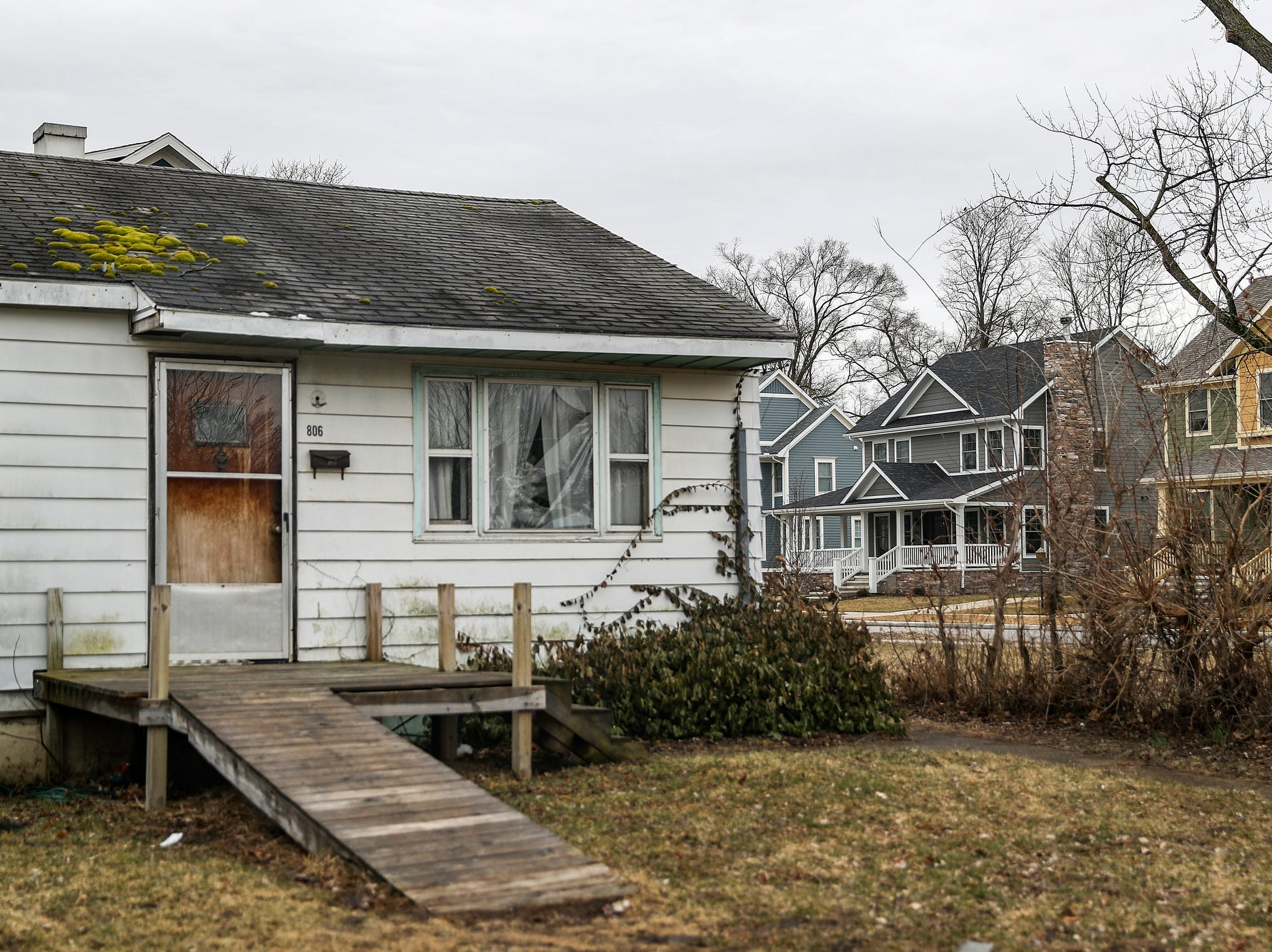 An older home sits with newer homes behind it, in the Harters Heights neighborhood near Notre Dame campus in South Bend, Ind. on Wednesday, March 13, 2019. Mayor Pete Buttigieg says $852 million in private investment has been spent on city-incentivized deals since he's been in office. New houses and commercial development are quickly on the rise near the university.