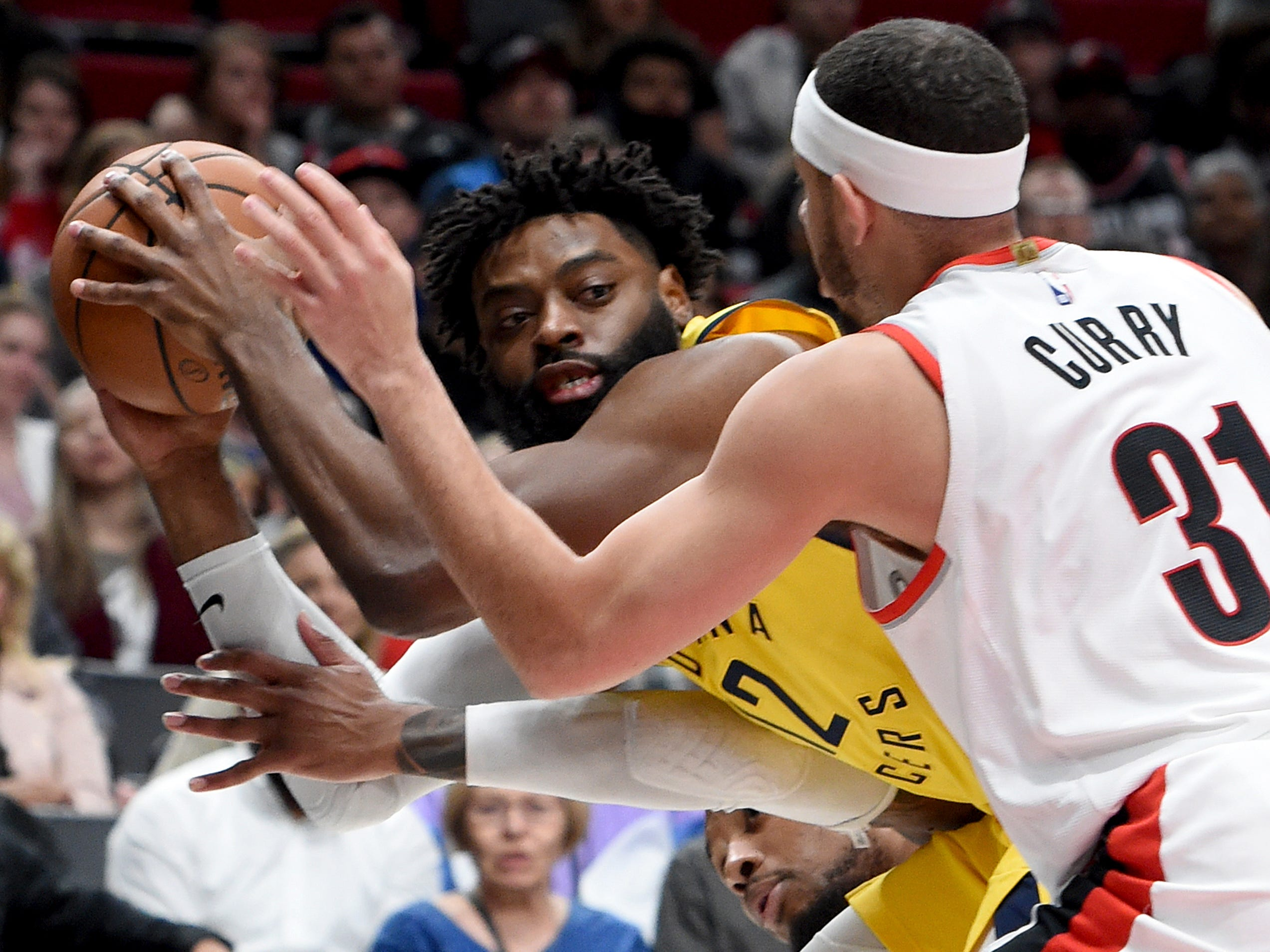 Indiana Pacers guard Tyreke Evans, left, looks to pass the ball as Portland Trail Blazers guard Seth Curry, right, defends during the first half of an NBA basketball game in Portland, Ore., Monday March 18, 2019.