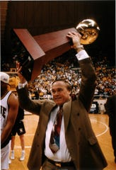 Purdue coach Gene Keady  shows off the Big Ten Championship trophy after their win over Illinois in 1994.