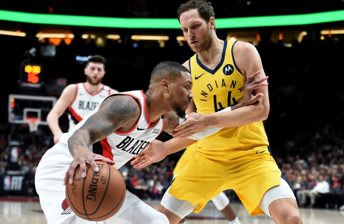 Portland Trail Blazers guard Damian Lillard, left, drives to the basket on Indiana Pacers forward Bojan Bogdanovic, right, during the first half of an NBA basketball game in Portland, Ore., Monday March 18, 2019.