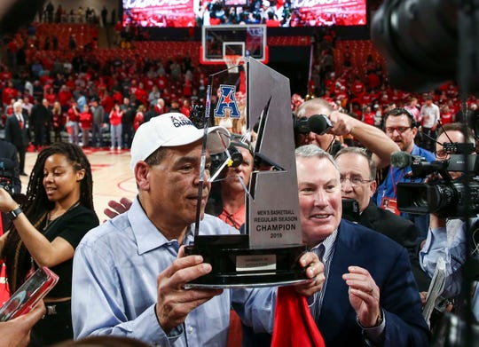 Houston Cougars head coach Kelvin Sampson holds the American Athletic Conference trophy after the Cougars defeated the Southern Methodist Mustangs at Fertitta Center.