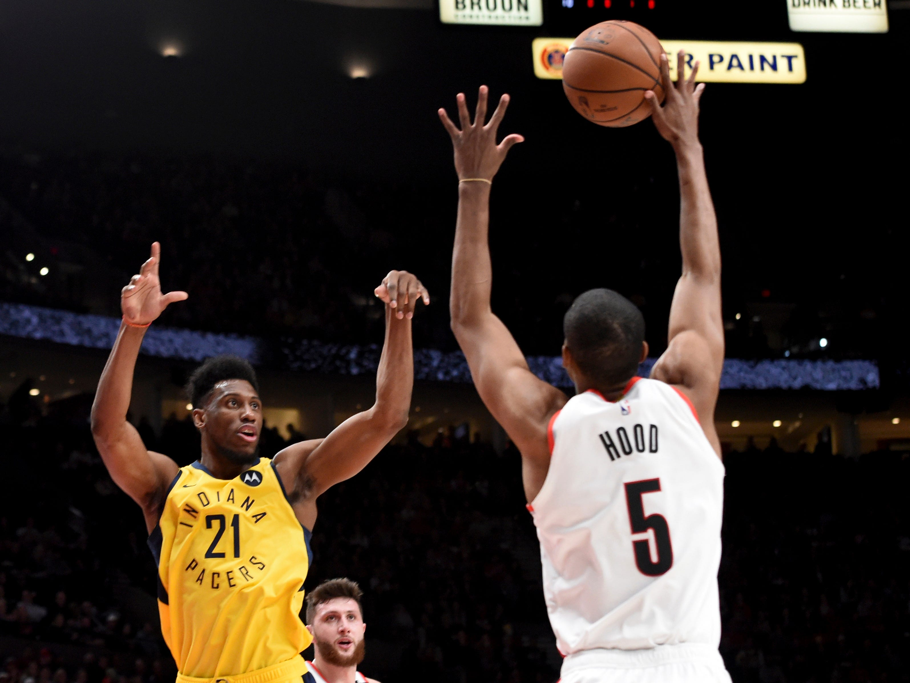 Indiana Pacers forward Thaddeus Young, left, tries to pass the ball over Portland Trail Blazers guard Rodney Hood, right, during the first half of an NBA basketball game in Portland, Ore., Monday, March 18, 2019.