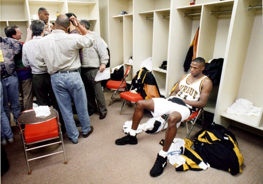 Herb Dove sits alone as Purdue teammate Glenn Robinson (back) is interviewed soon after the Boilermakers loss in the NCAA tournament on March 26, 1994.