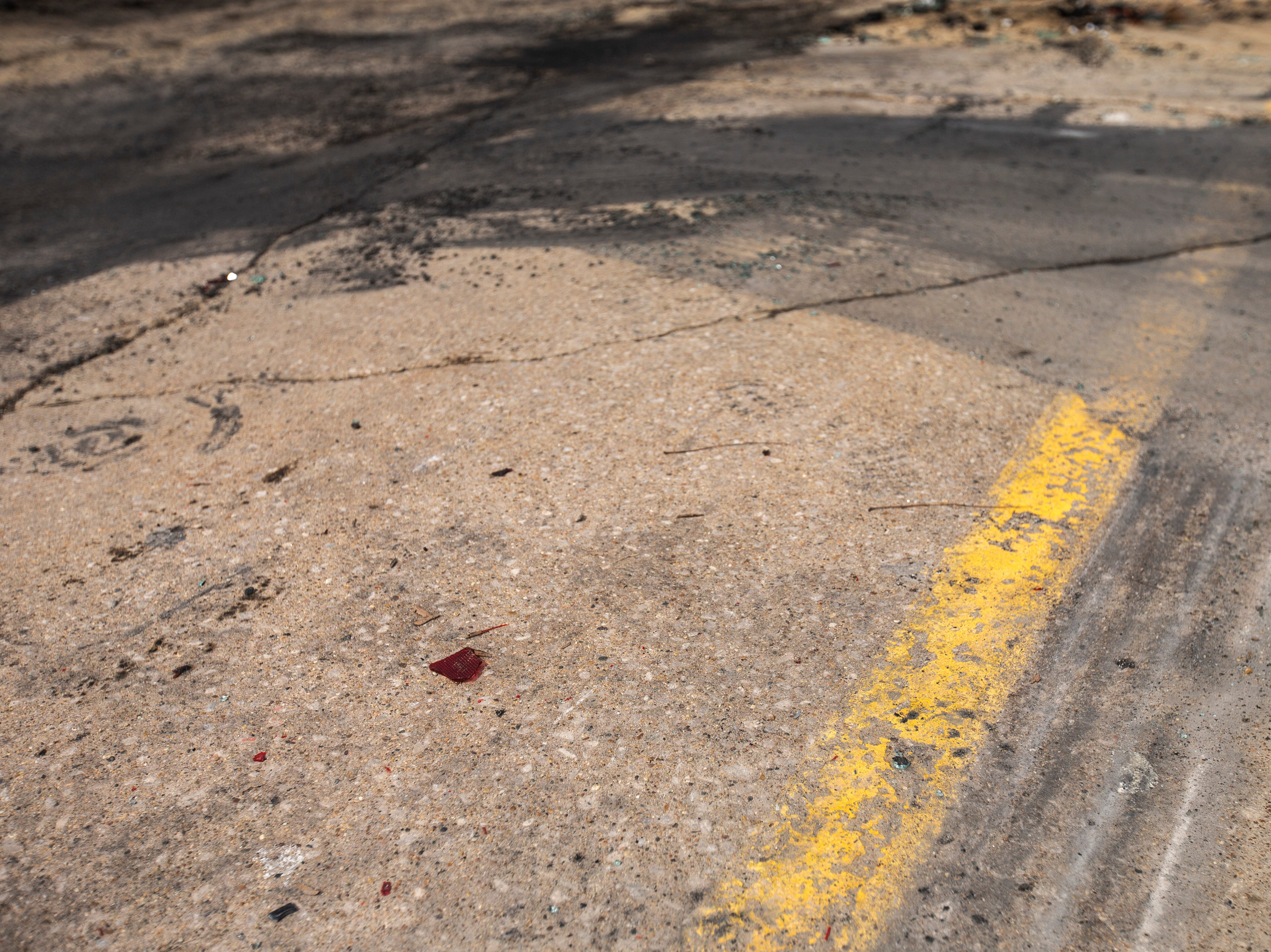 Tire marks lead away from the building where debris remains from a car fire, Tuesday, March 19, 2019, at 1213 Gilbert Court, in the parking lot of the former Crowded Closet store in Iowa City, Iowa. One person died in the car fire Monday night.