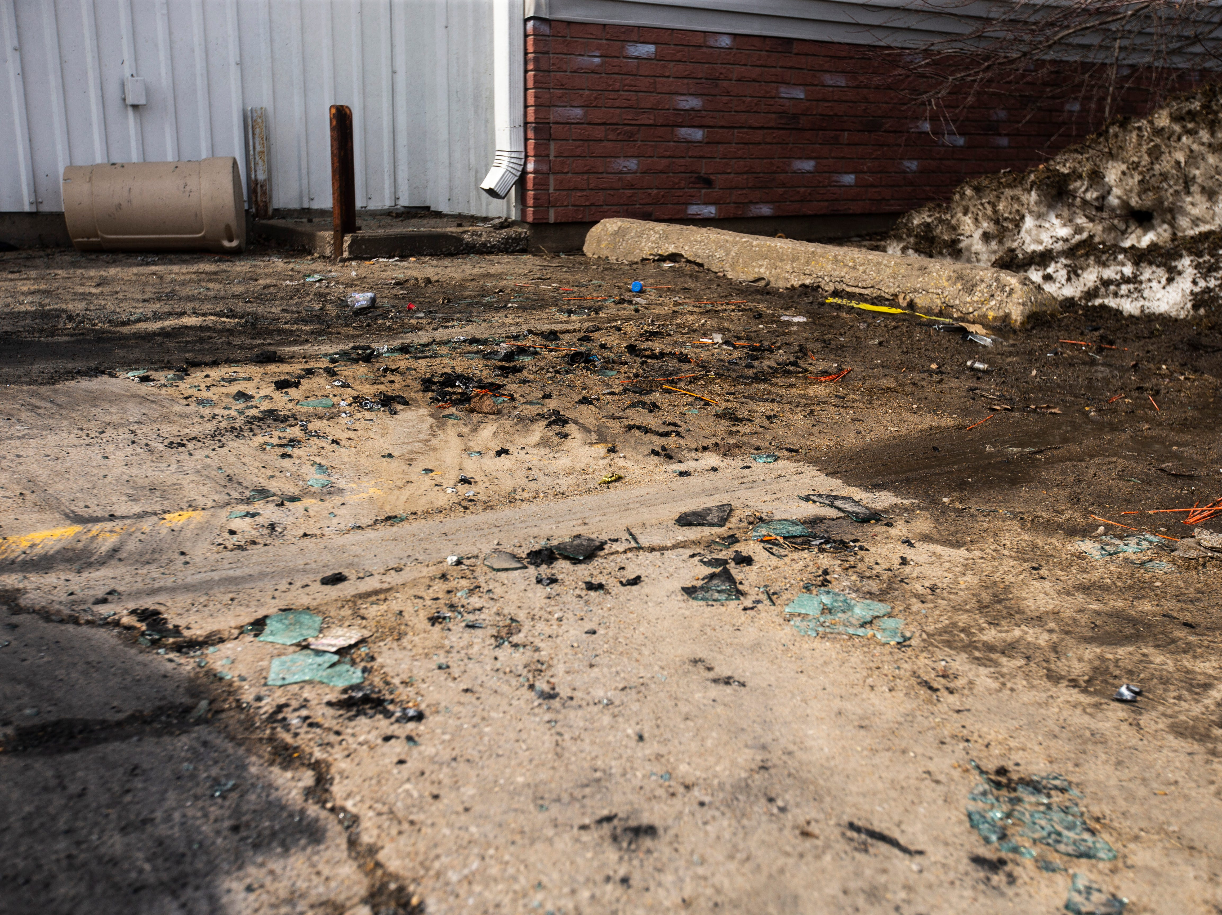 Debris remains from a car fire, Tuesday, March 19, 2019, at 1213 Gilbert Court, in the parking lot of the former Crowded Closet store in Iowa City, Iowa. One person died in the car fire Monday night.