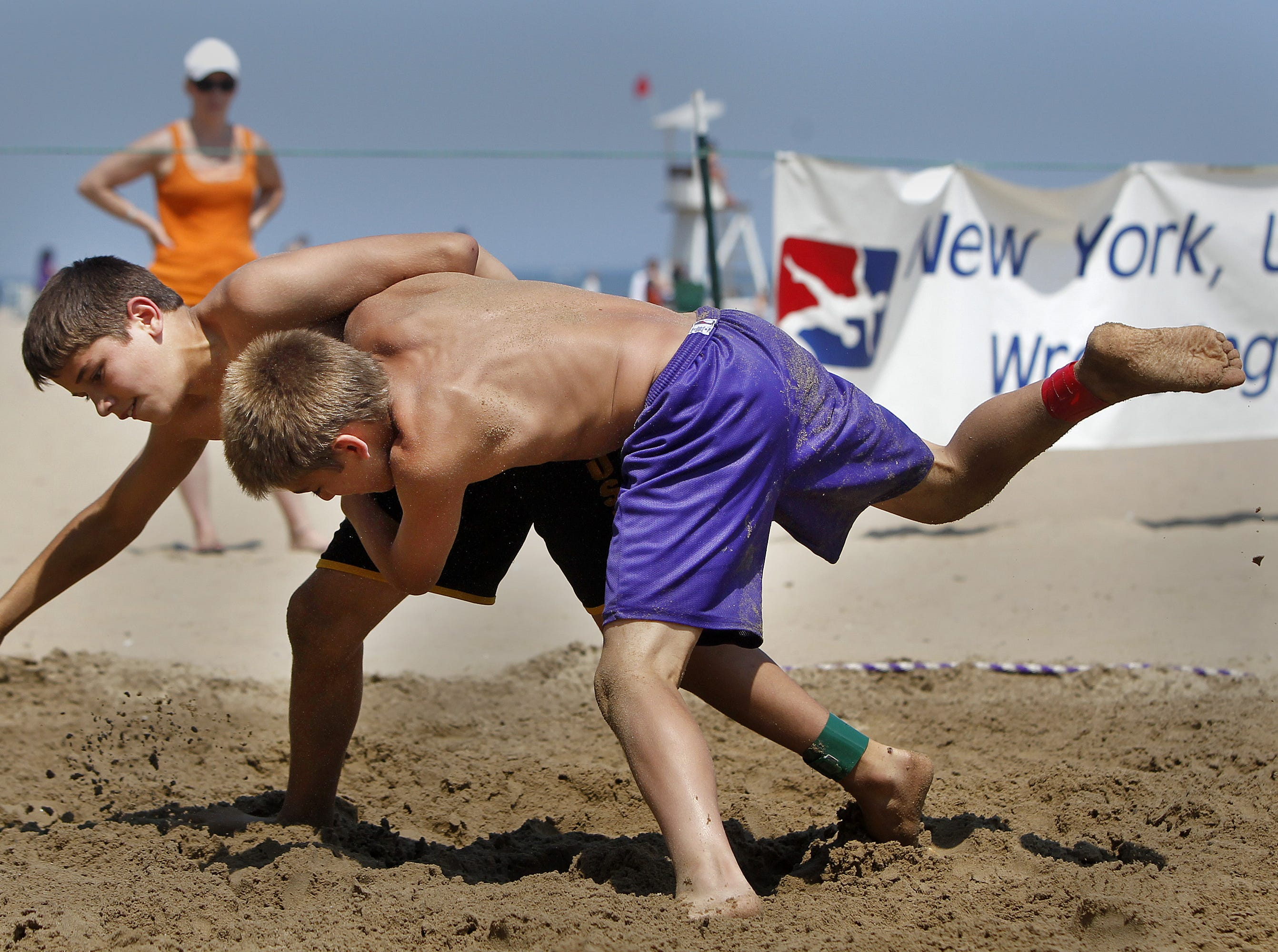 Yianni Diakomihalis, 12, of Greece, left, and Parker Kropman, 13, of Penfield, each look for the takedown in 103-lb. weight class during beach wrestling during the annual Ontario Beach Sports and Music festival, which included beach volleyball, sand wrestling, pickleball, and pole vault, Sunday afternoon, July 10, 2011.