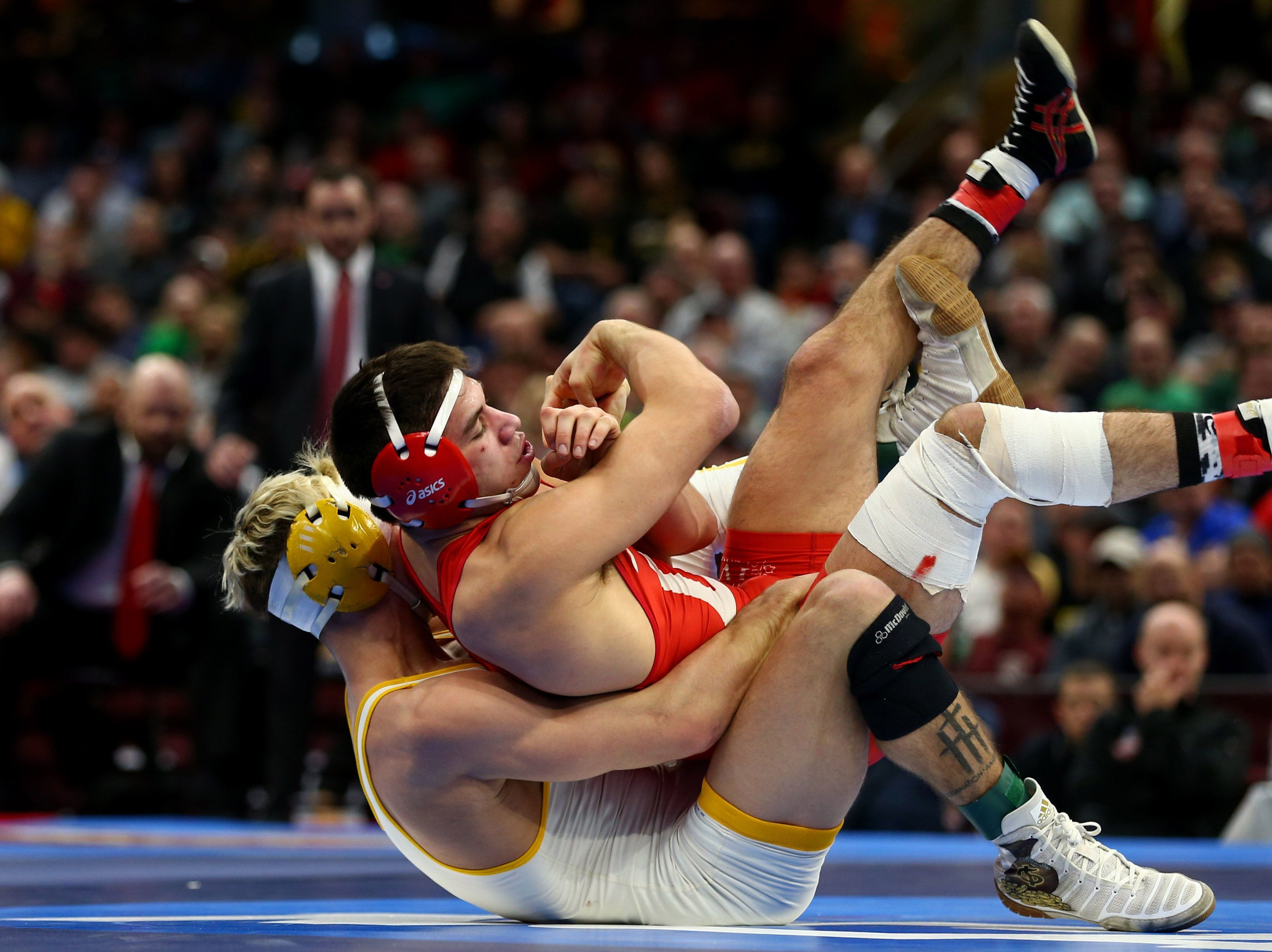 Wyoming  wrestler Bryce Meredith, white, competes against Cornell wrester Yianni Diakomihalis during the NCAA Wrestling DI Wrestling Championships at Quicken Loans Arena.  Photos by Aaron Doster/USA TODAY Sports Mar 17, 2018; Cleveland, OH, USA; Wyoming Cowboys wrestler Bryce Meredith (white) competes against Cornell wrester Yianni Diakomihalis (red) during the NCAA Wrestling DI Wrestling Championships at Quicken Loans Arena. Mandatory Credit: Aaron Doster-USA TODAY Sports