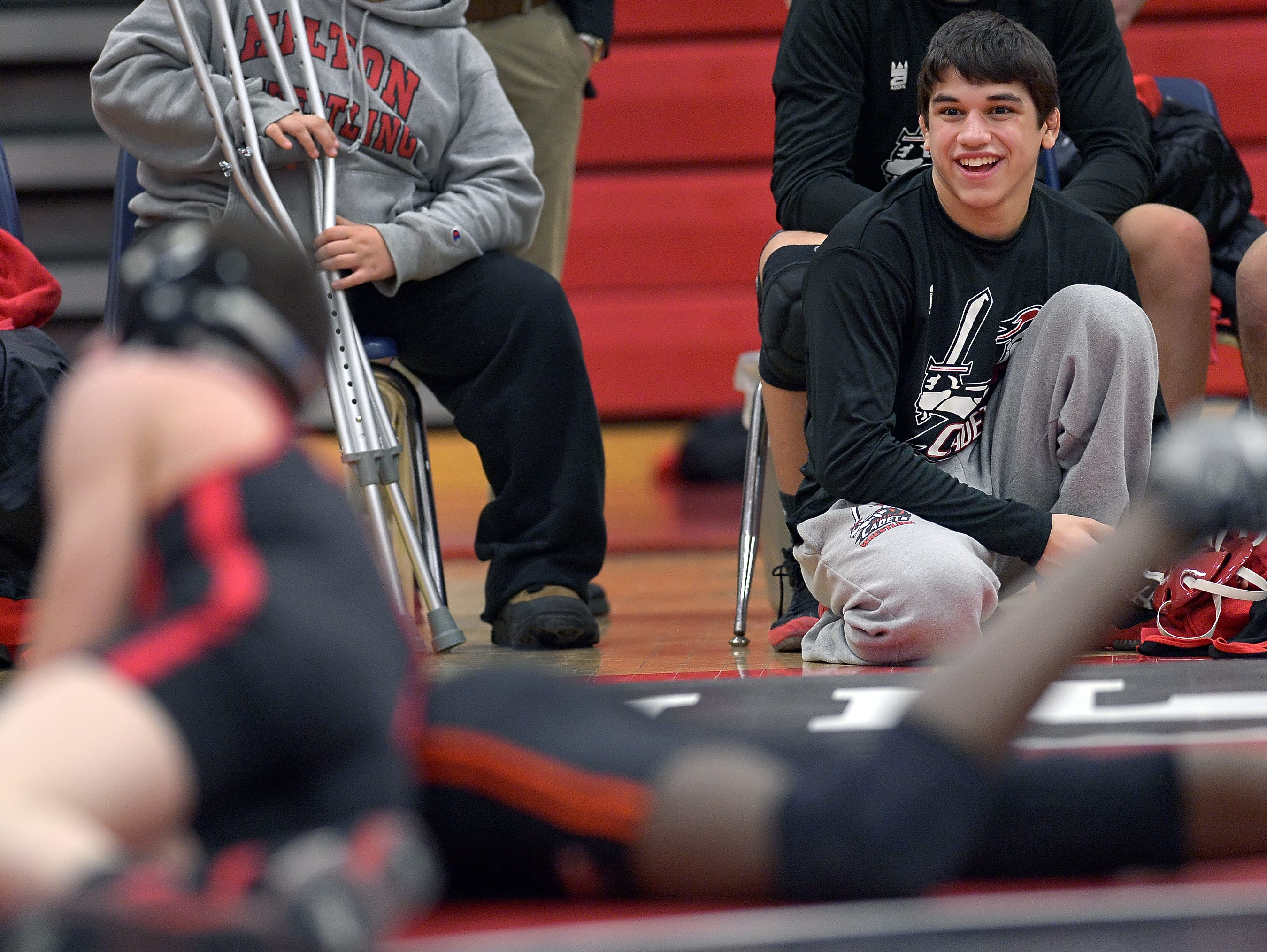 Hilton's Yianni Diakomihalis, right, whose 138 lb. match was forfeited, cheers on his teammates during regular season meet held at Hilton High School on Wednesday, January 13, 2016.