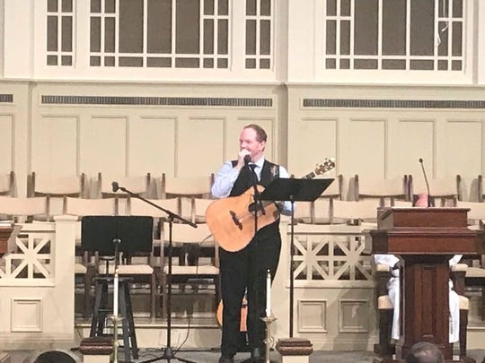 "Steven Whitson tells a story about John Kilzer before singing ""Farther Along"" at Kilzer's memorial service on Tuesday."