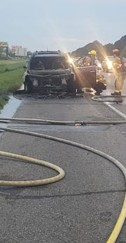 Firefighters extinguish Alfrelisha Thibeaux's car, which caught fire on the side of Interstate 10. Connor Manuel pulled over to help and signaled for her to get out of the car before it went up in flames.