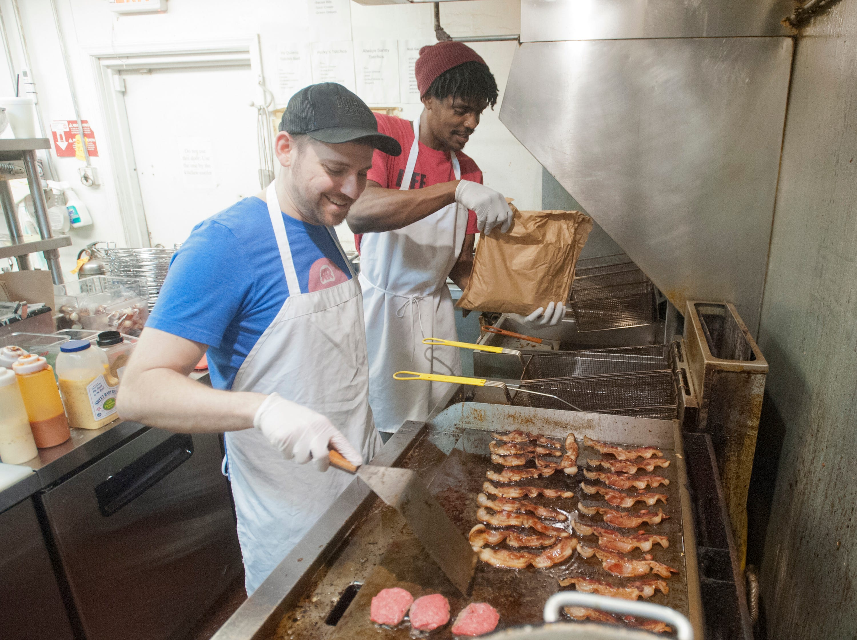 The Recbar's kitchen manager, Jon Quinter, left, tends to a grill filled with bacon as cook Will Breckinridge pours some tater tots into the fryer.14 March 2019