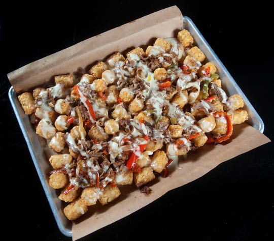 The Recbar's Always Sunny Totchos starts with tater tots that are deep fried. They are then covered with nacho ingredients queso cheese, Philly steak pieces, and a mix of sauteed onion and green and red bell pepper bits.
