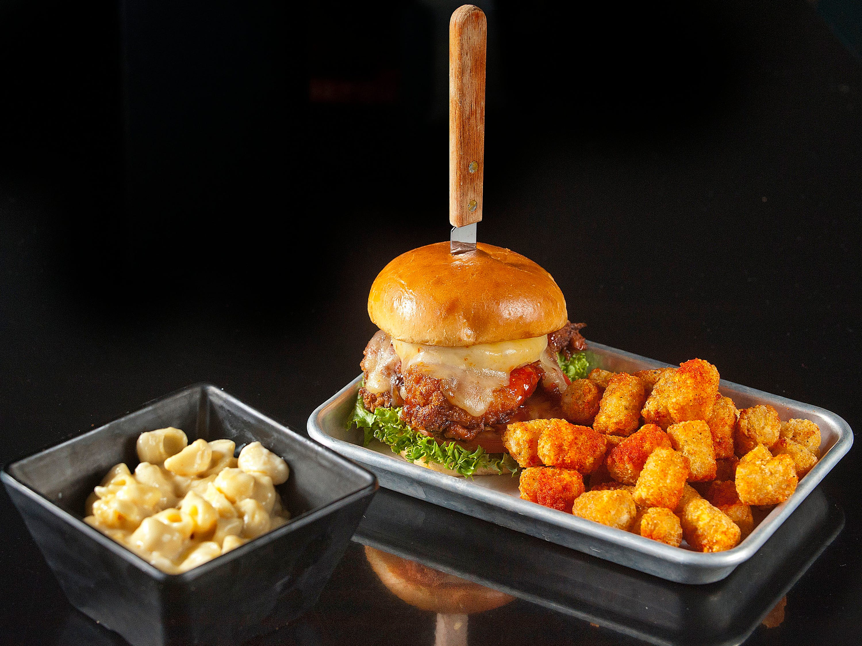 The Recbar's Sweet & Spicy Chicken Sandwich starts with a 6-oz. fried breast of chicken that has been tossed in a sweet and spicy sriracha sauce topped with lettuce, tomato, peperjack cheese and grilled pineapple. At left, is a side order of Mac n' Cheese.14 March 2019