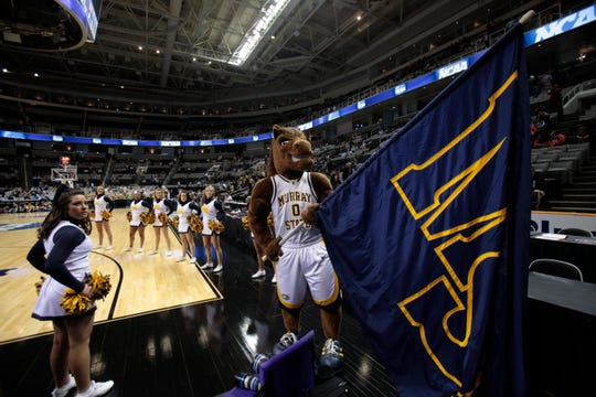 Murray State's mascot waves a flag during a basketball game.