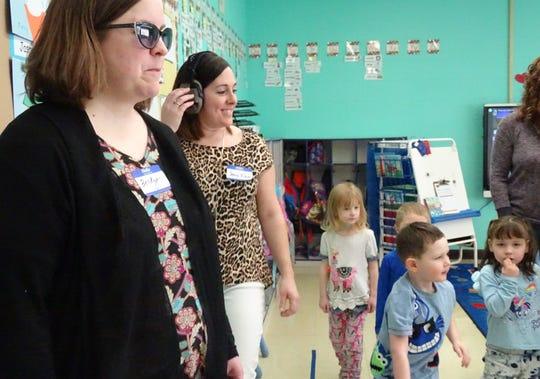 Becky Teynor, a service support administrator for Crawford County Board of Developmental Disabilities, left, and Jenny Klein of the Crawford County Health Department participate in a Fairway Preschool class while wearing devices to simulate autism spectrum disorder and hearing loss, respectively.