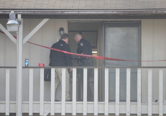 County coroner investigator Bob Ball enters an apartment at 650 Straub Road West on Monday after a man was shot and killed by police.