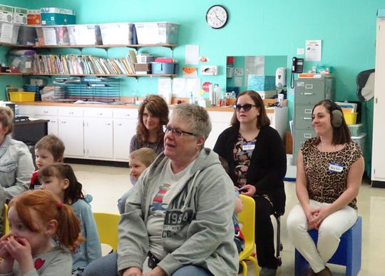 Seated at back left, Becky Teynor, a service support administrator for Crawford County Board of Developmental Disabilities and Jenny Klein of the Crawford County Health Department participate in a Fairway Preschool class while wearing devices to simulate autism spectrum disorder and hearing loss, respectively.