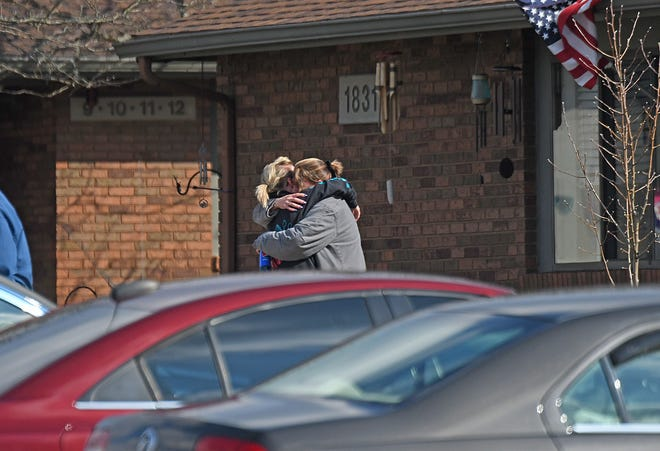 Two women embrace Tuesday morning outside the scene of a homicide at Morchester Villa Apartments on the corner of Straub Road and Middle-Bellville Road.