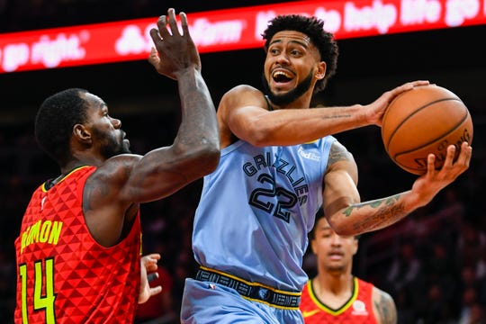 Memphis Grizzlies guard Tyler Dorsey looks to pass against the defense of Atlanta Hawks center Dewayne Dedmon (14) during the second half of an NBA basketball game, Wednesday, March 13, 2019, in Atlanta. The Hawks won 132-111. (AP Photo/John Amis)