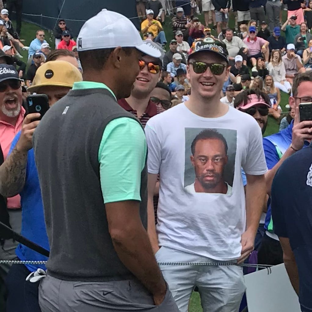 A New Berlin Eisenhower graduate drew a laugh from Tiger Woods for wearing the golfer's DUI arrest mugshot on a shirt