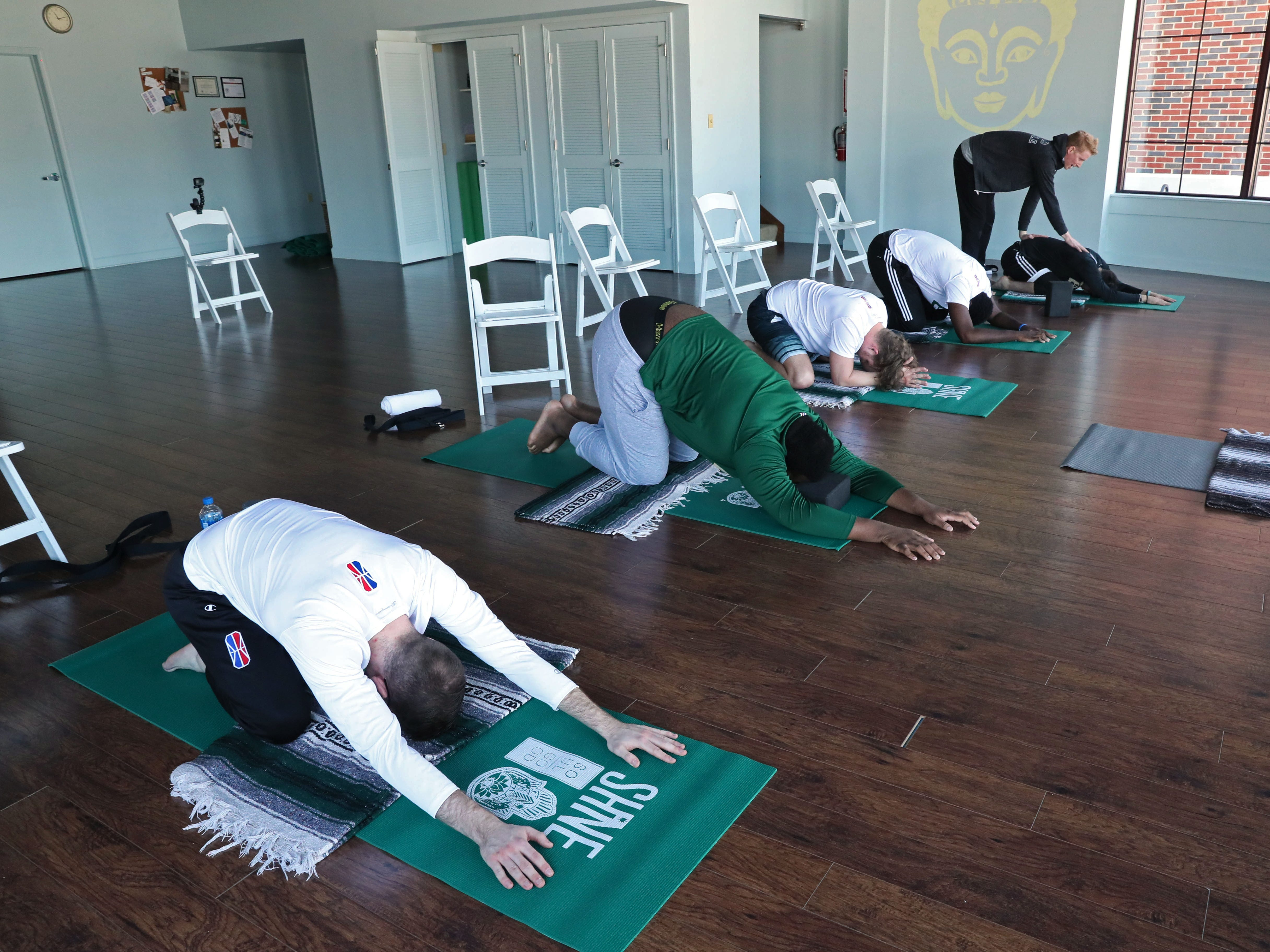 Members of the Bucks Gaming NBA2K team participate in a yoga class at Yoga On The Lake in Kohler as part of a wellness retreat.  Instructor Greg Cartwright teaches them yoga positions and stretches.