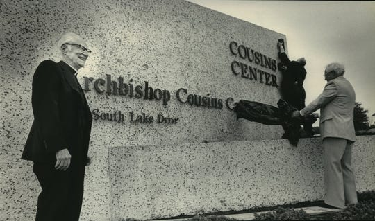 Archbishop Cousins smiles at left as Bishop Brust (top right) and Robert Chestnutwood  tear off the veils from the sign at front of the newly named Cousins Center in St. Francis in 1983.