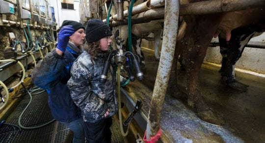 Kendra Thewis is aided by her 7-year-old daughter, Starr, with the chores in the milking parlor of the family farm near Mellen in rural Ashland County.