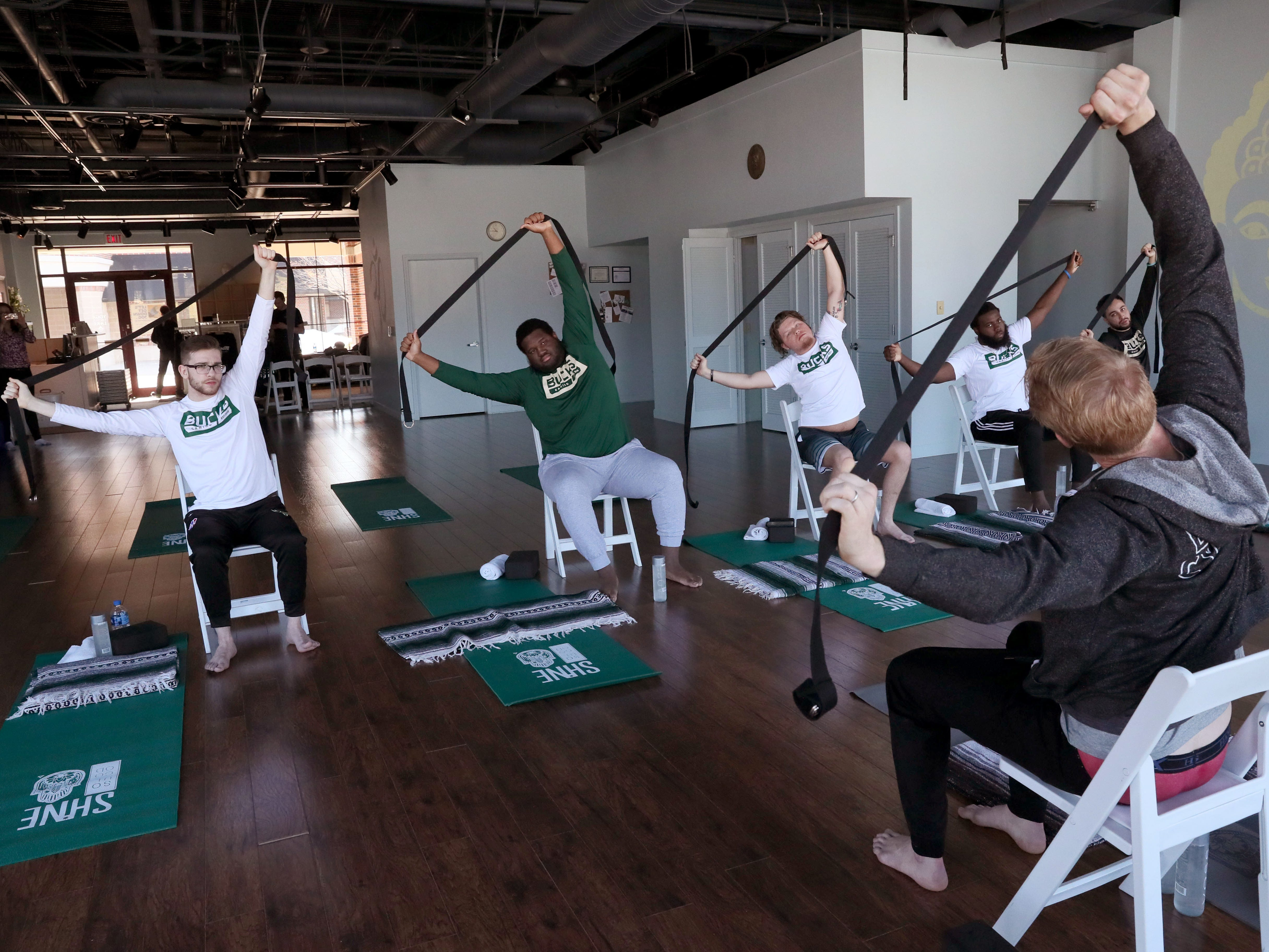 """Greg Cartwright (front) uses a nylon strap to stretch as he leads team members Stephen Lay (from left), Jovan Tenner, Robert """"Brandon"""" Harter, Aaron Rookwood and Chad Fodderie. The stretches will help the team loosen muscles that get tight because they spend so much time seated."""