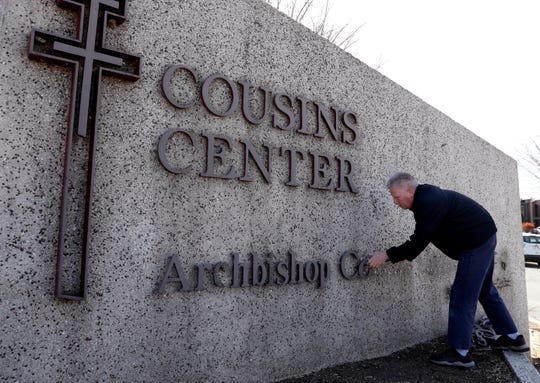 Steve Jupp, an Archdiocese of Milwaukee employee, removes the name of late Archbishop William E. Cousins from a stone monument outside the archdiocese's headquarters complex in St. Francis on Tuesday. The archdiocese announced it was removing the names of Cousins and Archbishop Rembert Weakland from key buildings in a sign of repentance for the church's mishandling of its sex abuse crisis.