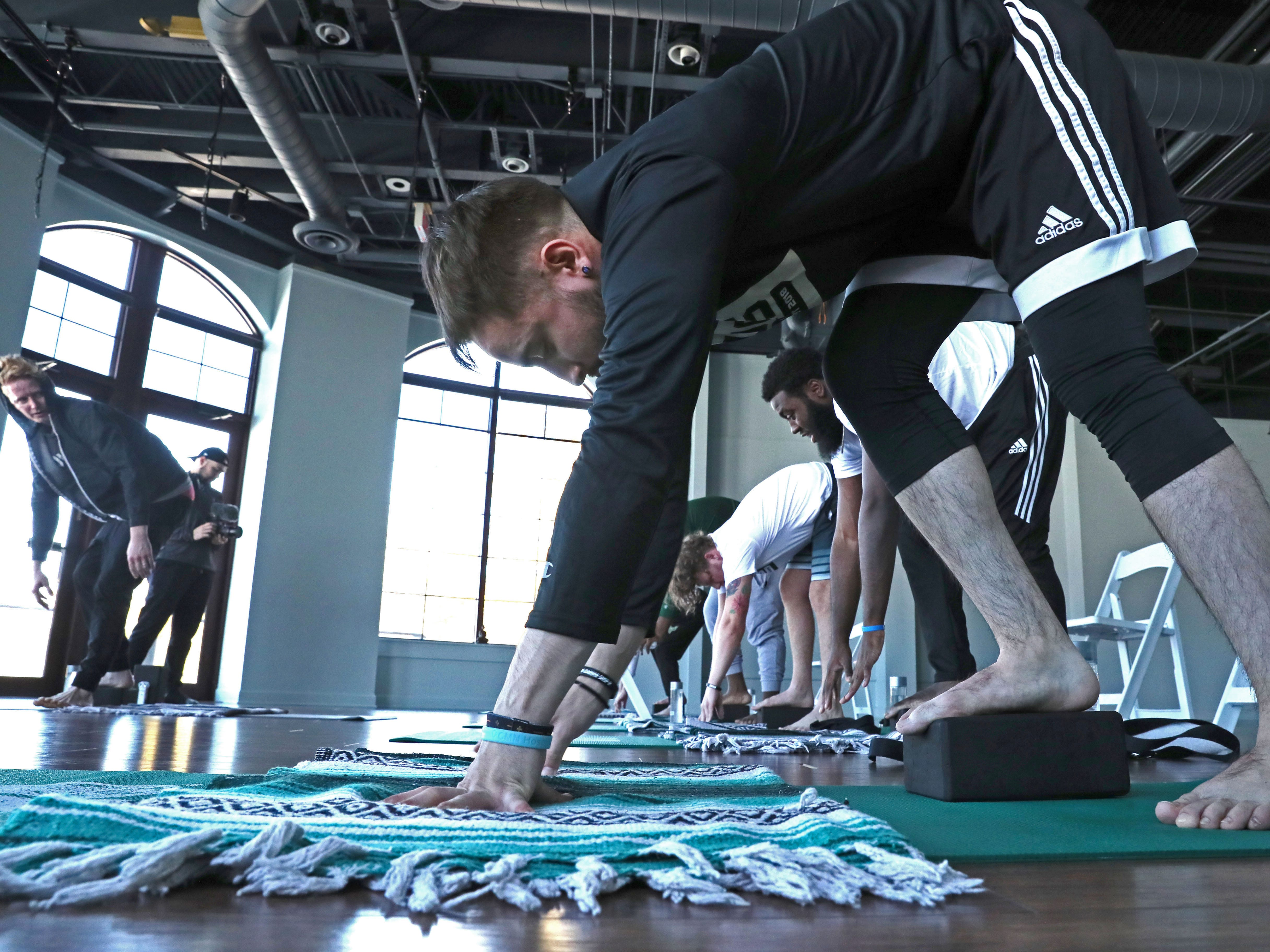 Bucks Gaming NBA 2K team member Chad Fodderie (foreground) listens to instructor Greg Cartwright (left) and moves into position as members of the team participate in a yoga class at Yoga On The Lake in Kohler.