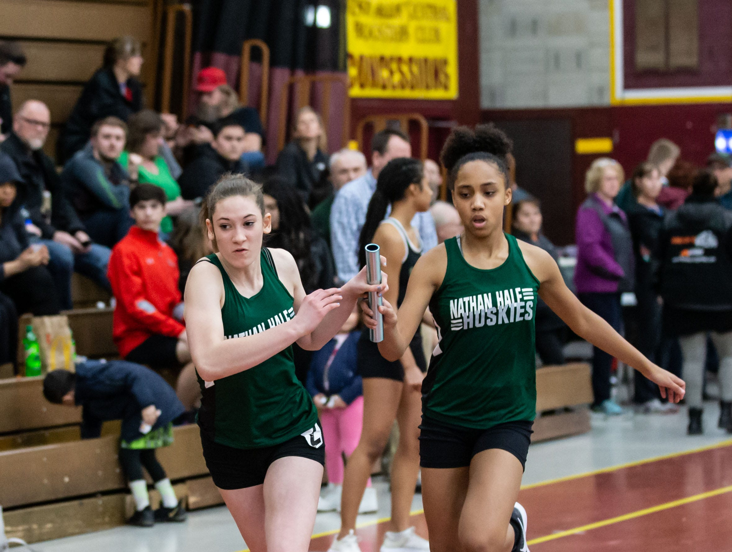 West Allis Nathan Hale's Julia Klein takes the baton from Alahna Patterson in the 4x160 meter relay while competing at the Reinhard Bulldog Relays hosted by West Allis Central on Friday, March 15, 2019.