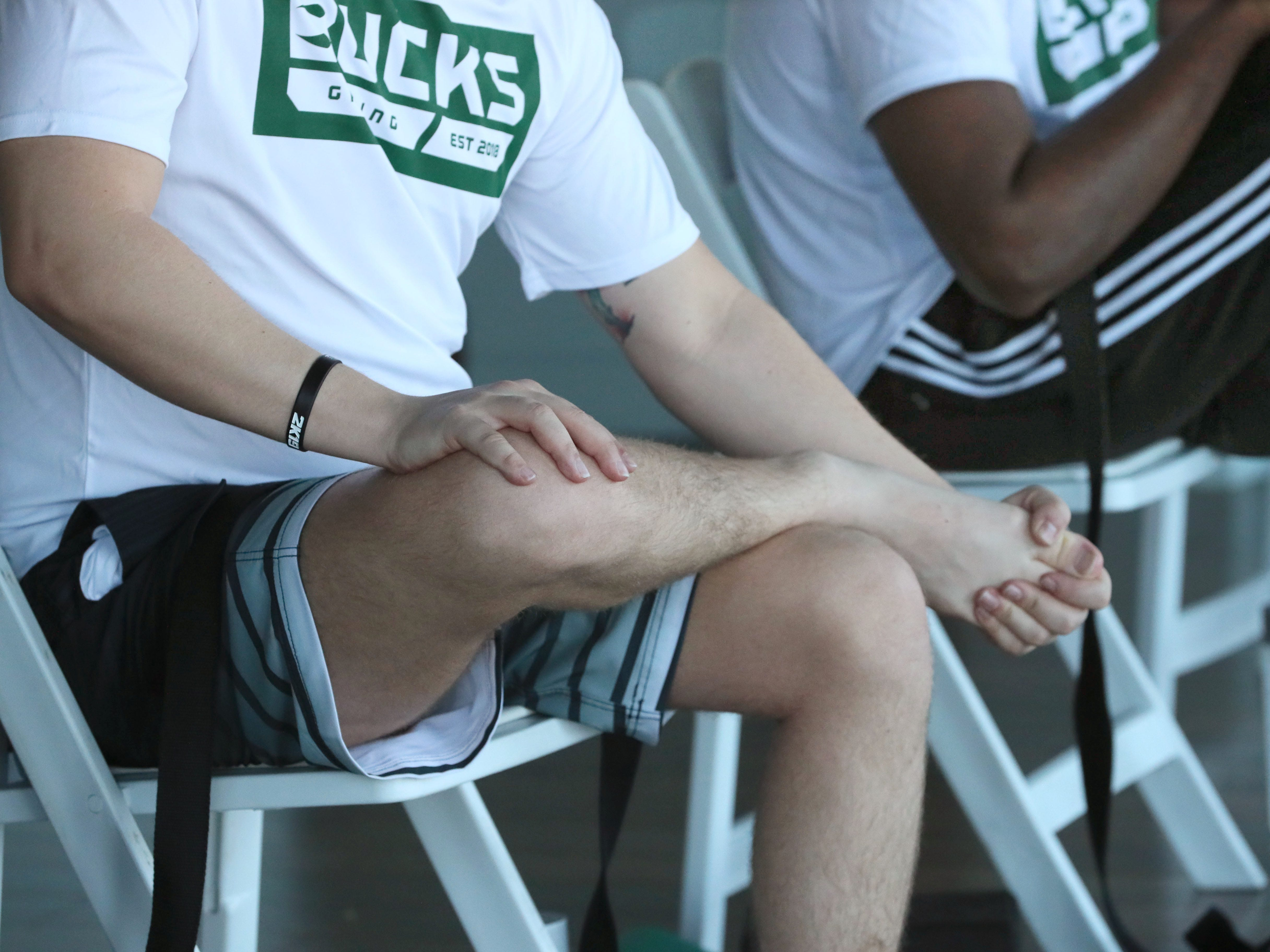 Team members learn how to move their legs while seated to relax their muscles.