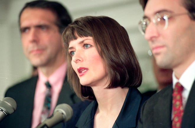 """In this Dec. 10, 1992 file photo, flanked by her attorneys Frank Morocco, left, and Sheldon T. Zenner, right, Lawrencia Bembenek answers questions at a news conference in Chicago, Ill. An attorney for Wisconsin's famous runaway convict and convicted murderer Laurie """"Bambi"""" Bembenek is asking Gov. Tony Evers for a posthumous pardon."""